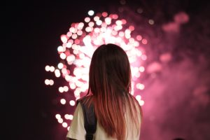 Asian girl silhouetted against pink fireworks in the distance
